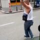 The driver waiting for his customer at the bus stop is dancing on the street in his spare time